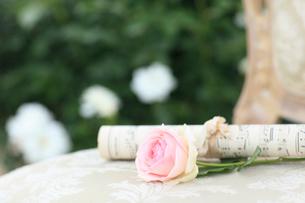 椅子の上の楽譜とバラの花の写真素材 [FYI02026004]