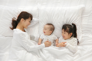 白い布団で眠るお母さんと赤ちゃんと女の子の写真素材 [FYI02026028]