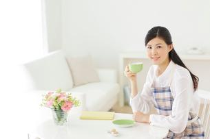 家事の合間にお茶を飲みくつろぐ若い主婦の写真素材 [FYI02026030]