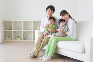 リビングのソファーに座る4人家族の写真素材 [FYI02026059]