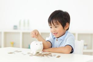貯金箱にお金を入れる男の子の写真素材 [FYI02026070]