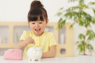貯金箱にお金を入れる女の子の写真素材 [FYI02026144]