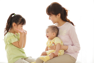 赤ちゃんを抱っこしたお母さんと女の子の写真素材 [FYI02026164]