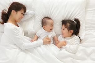 白い布団で眠るお母さんと赤ちゃんと女の子の写真素材 [FYI02026214]