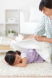 お昼寝をする女の子にブランケットをかけるお母さんの写真素材 [FYI02026216]