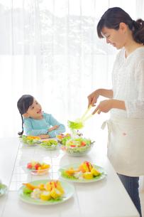 料理を作るお母さんを見つめる女の子の写真素材 [FYI02026248]