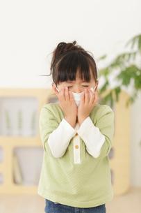マスクをしてくしゃみをする女の子の写真素材 [FYI02026309]