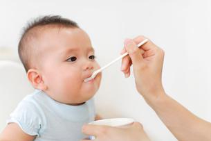 ベビーチェアに座って離乳食を食べる赤ちゃんの写真素材 [FYI02026317]