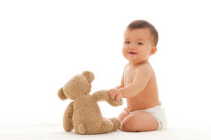 裸の赤ちゃんとくまのぬいぐるみの写真素材 [FYI02026330]