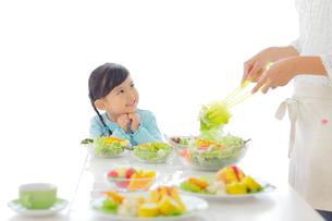 料理を作るお母さんを見つめる女の子の写真素材 [FYI02026345]