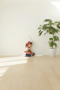 床掃除をして疲れて座り込む小さな女の子の写真素材 [FYI02026349]