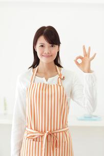 オッケーポーズをするエプロン姿の若い女性の写真素材 [FYI02026364]