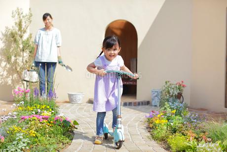 ガーデニングをするお母さんとキックスボードで遊ぶ女の子の写真素材 [FYI02026417]