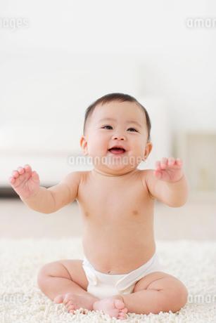 リビングでくつろぐ裸の赤ちゃんの写真素材 [FYI02026534]