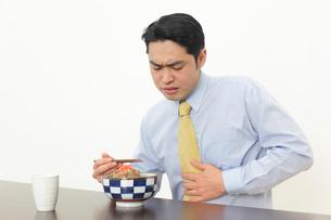 食事中に胃もたれを感じる男性の写真素材 [FYI02026537]