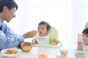 出勤前に朝食をとる共働き夫婦と双子の赤ちゃんの写真素材 [FYI02026605]
