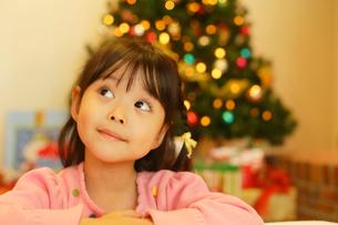 クリスマスツリーの前でプレゼントを想像する女の子の写真素材 [FYI02026623]