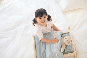 ぬいぐるみをおもちゃのベッドに寝かせて遊ぶ女の子の写真素材 [FYI02026677]