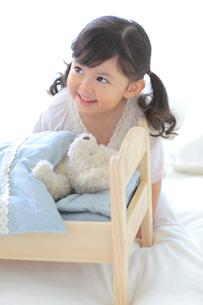 ぬいぐるみをおもちゃのベッドに寝かせて遊ぶ女の子の写真素材 [FYI02026686]