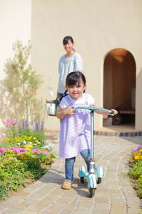 ガーデニングをするお母さんとキックスボードで遊ぶ女の子の写真素材 [FYI02026705]