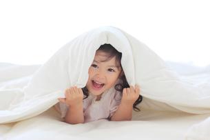 ベッドの上で布団をかぶり笑顔の女の子の写真素材 [FYI02026727]