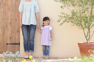 庭で手を繋いで並んで立つお母さんと女の子の写真素材 [FYI02026767]