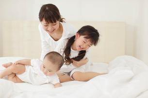 白いベッドの上のお母さんと赤ちゃんと女の子の写真素材 [FYI02026789]