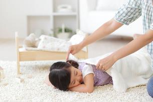 お昼寝をする女の子にブランケットをかけるお母さんの写真素材 [FYI02026825]