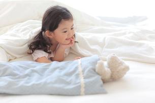 ベッドの上で布団に入りぬいぐるみと遊ぶ女の子の写真素材 [FYI02026838]