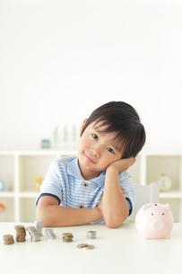 貯金箱の前で悩む男の子の写真素材 [FYI02026897]