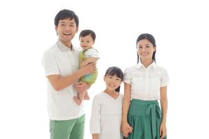 爽やかな緑の服を着た両親と女の子と赤ちゃんの写真素材 [FYI02026946]