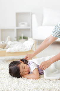 お昼寝をする女の子にブランケットをかけるお母さんの写真素材 [FYI02026960]