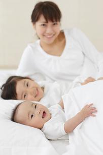 白い布団で眠るお母さんと赤ちゃんと女の子の写真素材 [FYI02027022]