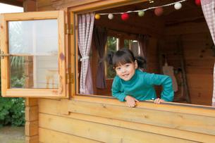 ログハウスの窓から顔を覗かせる女の子の写真素材 [FYI02027066]