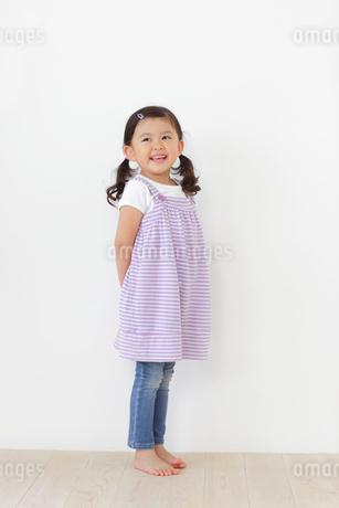 フローリングの床に立つ小さな女の子の写真素材 [FYI02027114]