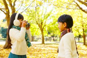 紅葉のきれいな秋の公園で写真を撮る子供達の写真素材 [FYI02027129]