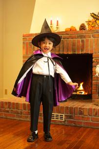 暖炉の前でハロウィンの仮装をする男の子の写真素材 [FYI02027132]