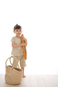 かごバックとバゲットを抱える女の子の写真素材 [FYI02027150]