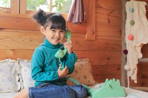 ログハウスで電話をかける女の子の写真素材 [FYI02027204]