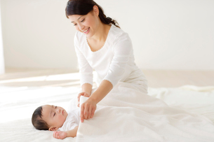 眠る赤ちゃんと見守るお母さんの写真素材 [FYI02027220]