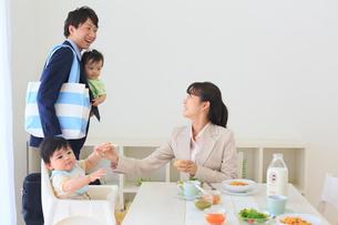 慌ただしく出勤準備をする共働き夫婦と双子の赤ちゃんの写真素材 [FYI02027299]