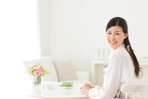 家事の合間にお茶を飲みくつろぐ若い主婦の写真素材 [FYI02027325]