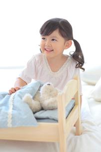 ぬいぐるみをおもちゃのベッドに寝かせて遊ぶ女の子の写真素材 [FYI02027328]