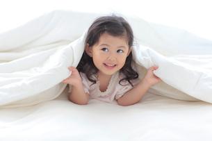 ベッドの上で布団をかぶり笑顔の女の子の写真素材 [FYI02027329]