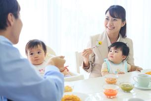 出勤前に朝食をとる共働き夫婦と双子の赤ちゃんの写真素材 [FYI02027378]