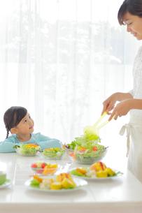 料理を作るお母さんを見つめる女の子の写真素材 [FYI02027451]