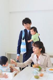 慌ただしく出勤準備をする共働き夫婦と双子の赤ちゃんの写真素材 [FYI02027600]