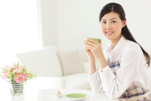 家事の合間にお茶を飲みくつろぐ若い主婦の写真素材 [FYI02027603]