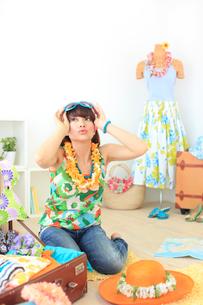 サングラスをかけながら夏の旅行の準備をする若い女性の写真素材 [FYI02027624]