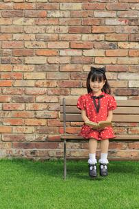 レンガ壁の前のベンチに座って読書をする女の子の写真素材 [FYI02027728]